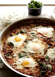 baked eggs in a skillet with tomatoes lentils and spinach serve with whipped goat