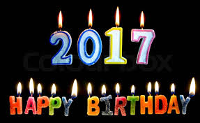 colourful of 2017 happy birthday candle with flame lighting on the black screen stock photo