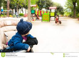 Little Baby On Stroller Looking At Games In City Garden Stock Photo ...