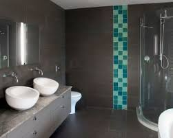 men bathroom desiign with black tile floor and wall with monochromatic blue tile accent and corner shower section with glass partition and also double