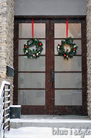 the green wreaths with flocked pinecones and shiny ornaments look very festive hanging from red ribbons on the outside of our front doors