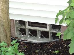glass block basement window in a well for security light transmission