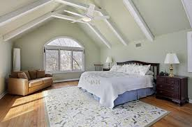 simple master bedroom with a large bed and a brown couch on the corner the