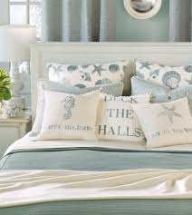 light blue and white beach bedroom bedding set with seashell starfish and seahorse images on the pillows