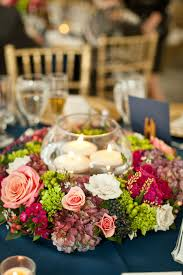 floating candle centerpiece in round glass vase With flowers around