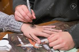 A Young Lady Uses A Pen To Draw A Design On The Hand Of A Girl