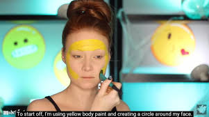 lex creates the yellow base with face paint and a foundation brush