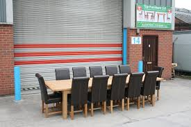 2 9 3 4m tallinn table and 12 dark brown titan leather chairs outside out uttoxeter warehouse