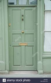 green painted wooden paneled front door no 90 with br knocker letterbox and of house in uk