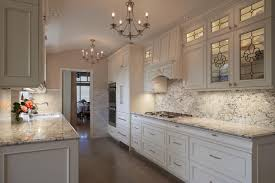 2 chandeliers white marble countertop and cabinets sink faucet gas cooktop