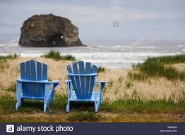 adirondack chairs on beach. Two Blue Adirondack Chairs On A Grassy Beach With Rock Formations In The  Ocean; Rockaway Oregon United States Of America