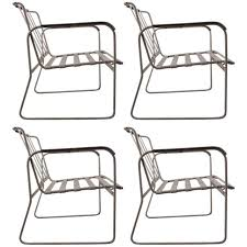 set of four wrought iron and plastic strap garden patio chairs for