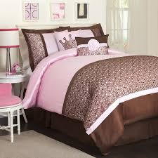 interior pink and dark brown bedding set on the bed connected by three white picture