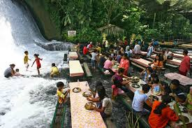 A restaurant where you eat barefoot in water from a waterfall - Villa  Escudero Philippines.