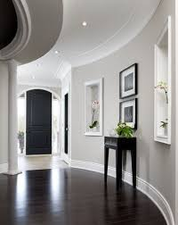 transitional hall hallway designs with light gray wall paint color also dark brown laminate floor and black small modern console table also shelf with black furniture wall color