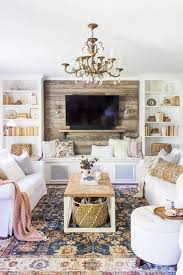 a bright eclectic space with rustic touches and two white sofa accessorized with pastel pillows