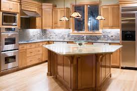 oak kitchen cabinets with quartz countertops. unique pentagonal island stands out in this richly textured kitchen. multicolored brick backsplash unites upper oak kitchen cabinets with quartz countertops