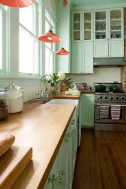 a mint green kitchen with c lamps and natural wood countertops for a vintage feel