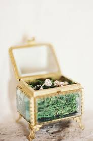 sheer glass and gold ring box on legs with moss