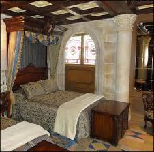 A Medieval design bedroom. I see dark wood furnishings &' wooden beams on  celling. Walls are solid stone white &' few decorative molding on the  portico&' ...