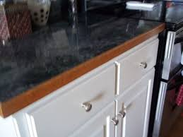 i went with a gray marble formica for the countertops with white cabinets while i was at work the man that made the cabinets had put the stained oak edging
