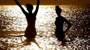 happy woman on vacations people sillhouette in water on sunrise sunlight reflection in water two young women in ocean on sunset sea sunset beauty