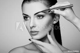 beautiful brunette woman paints the eyebrows beautiful woman face makeup detail beauty