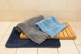 our four bath mat picks stacked on top of each other sitting on pale tiled