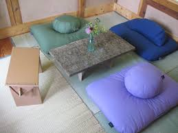 small space living room decor using rectangle coffee desk and floor seating cushions for asian style interior decor