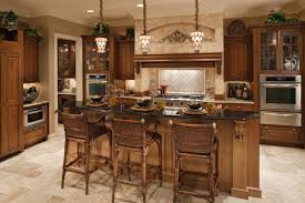 kitchen design cabinets traditional light: kitchen centered around lush wood island with raised black marble dining surface over beige tile