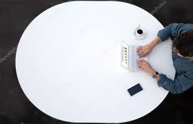 white office round table and man working on computer top view casual clothing typing on keyboard with marketing chart on screen smart phone and cup of