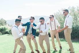 groom navy jacket beige pants light green tie sunglasses groomsmen white shirt green bowtie leather suspenders