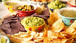 bowls of food including fresh guacamole and corn chips crowd a table