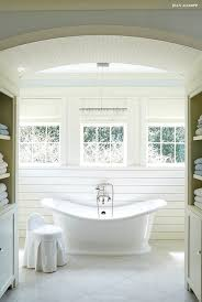hall with barrel ceiling flanked by recessed line shelves and cabinets leading to a bathroom boasting a linear crystal chandelier hanging over a white