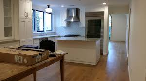 white shaker cabinets with super white quartz counter tops and wood flooring kitchen remodeling services in orange county ca