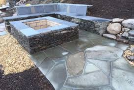 stacked stone fire pit with irregular flagstone patio