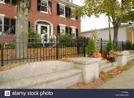 wrought iron fence brick. A Black Wrought Iron Fence By Red Brick Colonial Style House. There Is Cement Sidewalk And Bench. The Season Aut