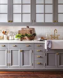 gray cabinets with white subway tile backsplash and brass hardware