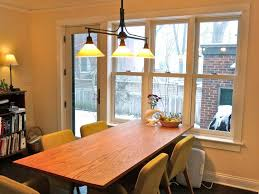 triple pendant lighting for dining room lights with small rectangular table and beige backdrop