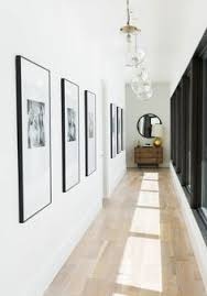 Pendant lights by Arteriors hang in the light-filled hallway |  archdigest.com