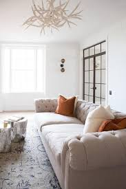 accented with ivory and burnt orange pillows a tan tufted sofa sits on a gray and blue rug facing a silver tree stump accent table illuminated by a faux