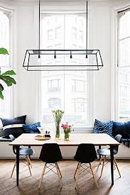 bright dining space with a large pendant light and a bench