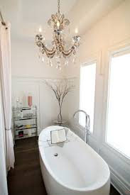 artistic small bathroom chandeliers over tub with crystals accent design and gold frame create luxury