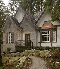 A grey stone home exterior with iron guardrail and copper awning. This is  an English
