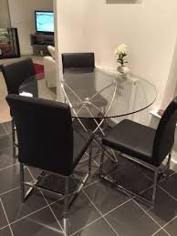 dwell glass round dining table and 4 black chairs