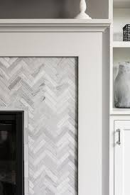 gorgeous fireplace is ed with a white fireplace mantle framing gray herringbone marble surround tiles