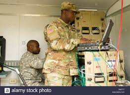 Sgt. John Powell (foreground) and Spc. Jesse Fields, information technology  specialists, from Chemical Biological Radiological Nuclear and Explosives  Coordination Element 3 prepare and troubleshoot their Secure Internet  Protocol Router Network (SIPR ...