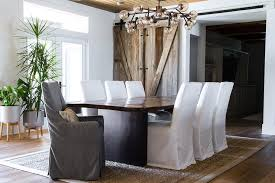 hangs from a plank ceiling above a live edge dining table seating white slipcovered dining chairs and gray slipcovered head chairs on a bound jute rug