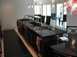 incridible black granite top kitchen island with seating and stove tops as well as three hanging lamps in open kitchen decor ideas
