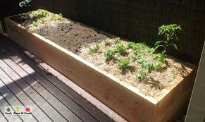 a long narrow cypress garden bed ready for planting herbs